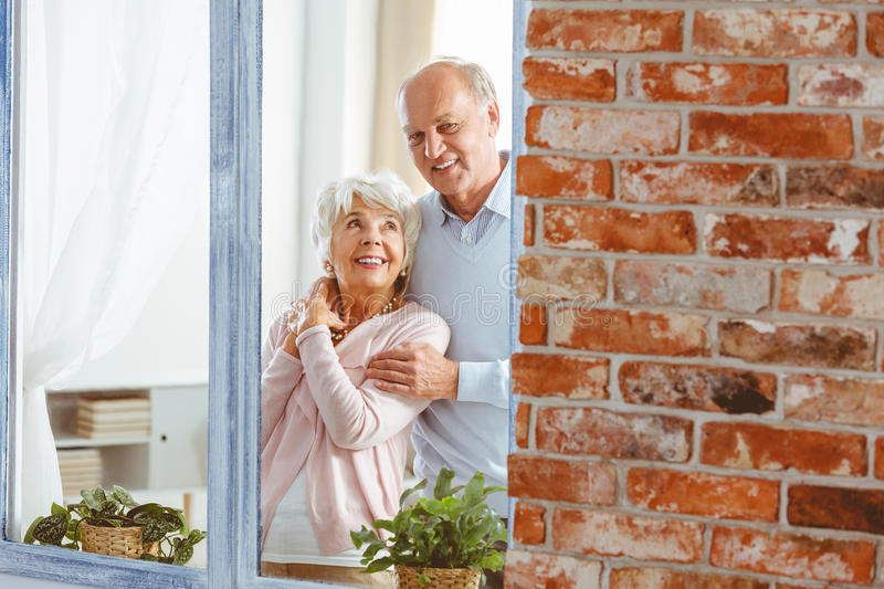 Married couple by the window. Married couple of seniors smiling and standing together by the window stock image