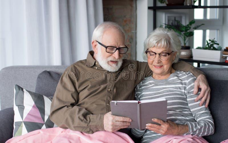 Married envelheceu os pares que olham no álbum de fotografias fotografia de stock royalty free
