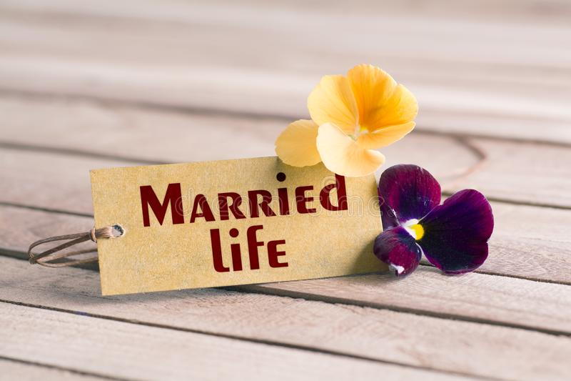 Married life tag. Tag banner married life and violet flower on wooden desk royalty free stock photography