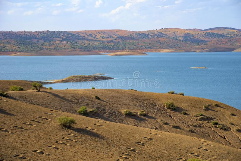 Marroko, lake water reservoir in the Atlas Mountains seen from a high point of view, with deep blue water, and tall bald striped. Marroko, lake water reservoir royalty free stock photos