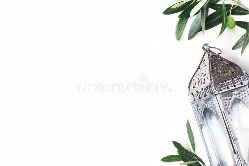 Marroquí de plata del vintage, linterna árabe Hojas verdes y ramas del olivo aisladas en el fondo blanco de la tabla foto de archivo libre de regalías