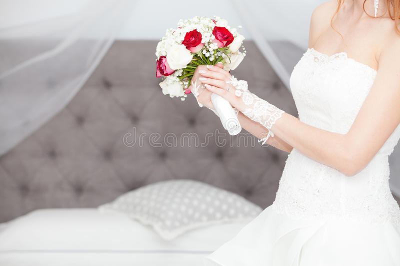 Marry, marriage bouquet and wedding dress. Bride at home. Bridal bed. Figure of a woman with a bouquet of flowers in her hands in front of the bridal bed in the royalty free stock photo