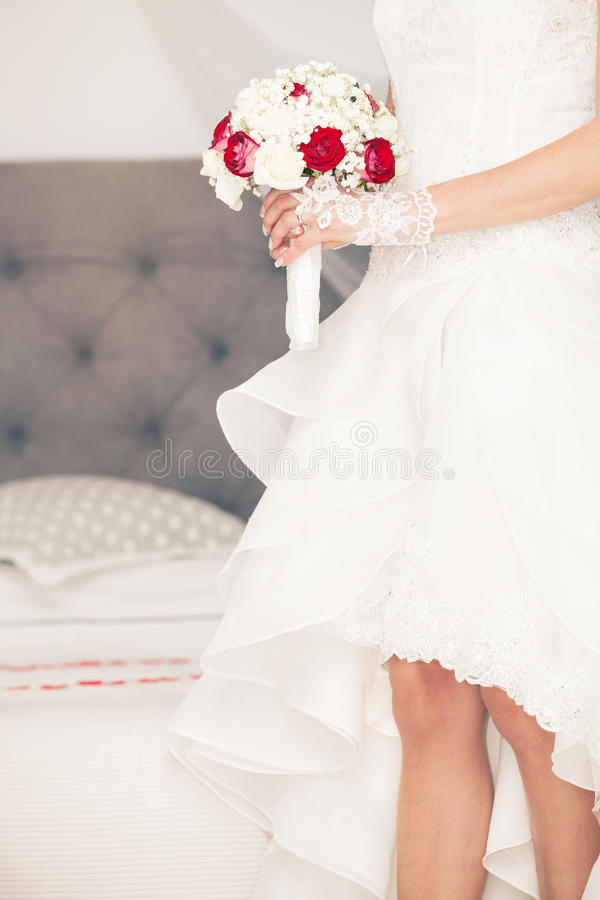 Marry, marriage bouquet and wedding dress. Bride at home. Bridal bed. stock photography