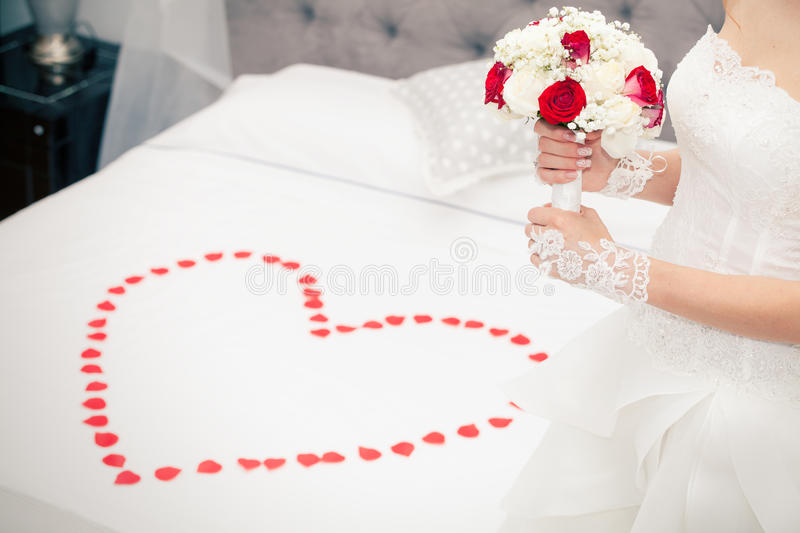 Marry, marriage. Bride at home. Bridal bed. Petals heart shape. Figure of a woman with a bouquet of flowers in her hand in front of the bridal bed in the bedroom stock image