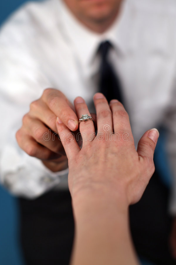 Marry me?. A man proposing and putting a ring on a woman's finger royalty free stock photography