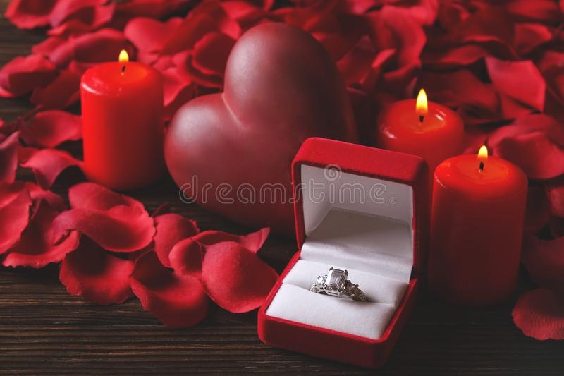 Conceptual photo of wedding or engagement ring with candles in shape of heart. St. Valentine`s day stock images