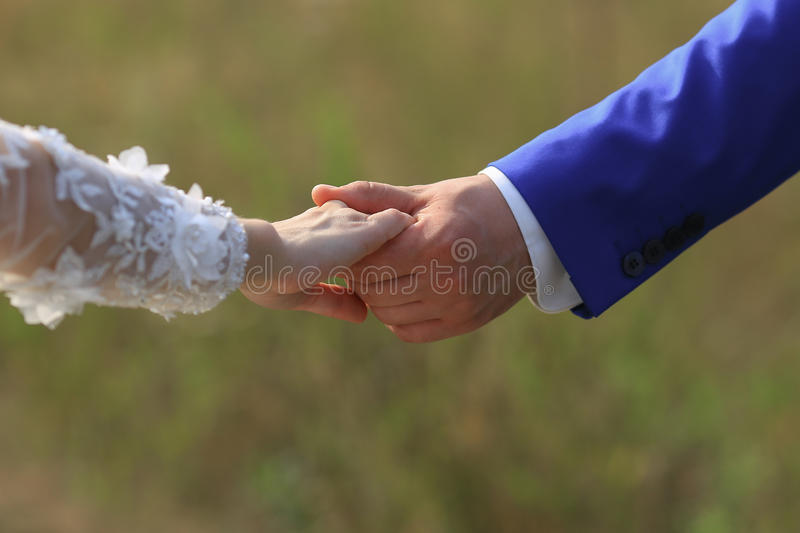 Marry me today and everyday. Newlywed couple holding hands, wedding picture. stock photography