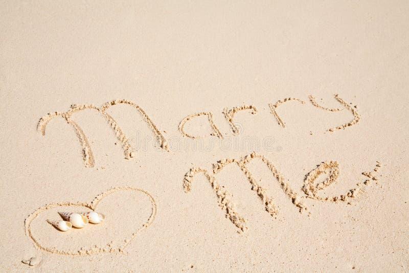 Marry me written on sand. Marry me written on white sandy beach stock photos