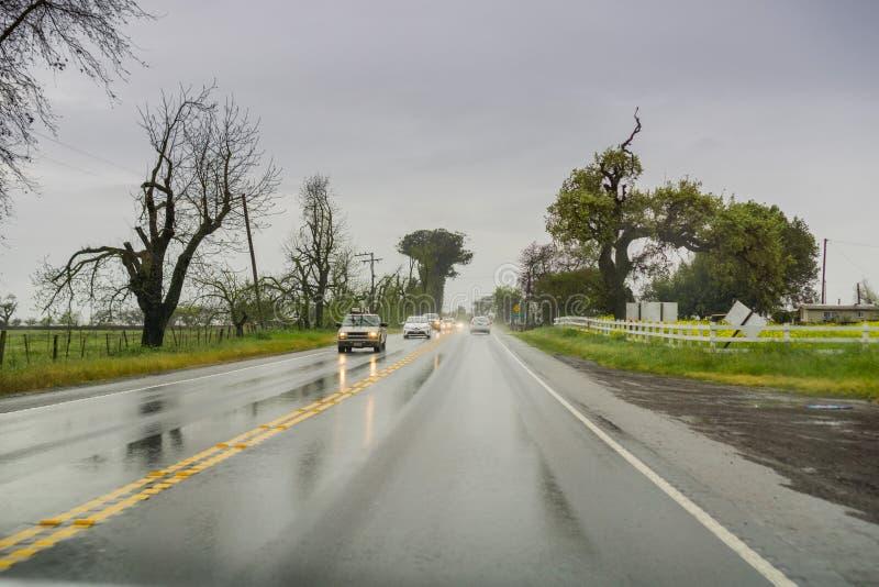 Mars 20, 2017 Gilroy/CA/USA - köra till och med regn på en våt väg royaltyfri foto