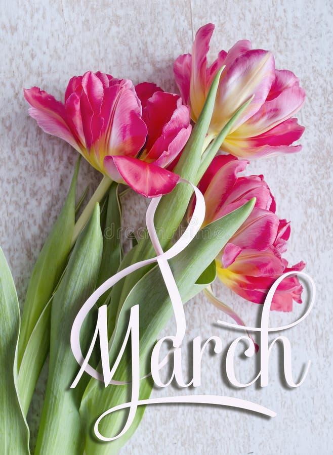 8 mars, internationella kvinnors kort för daghälsning Vitt diagram åtta och en bukett av tre röda tulpan royaltyfri foto