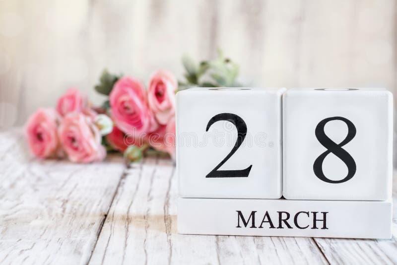 28 mars Kalenderblock med rosa Ranunculus i bakgrunden arkivbild