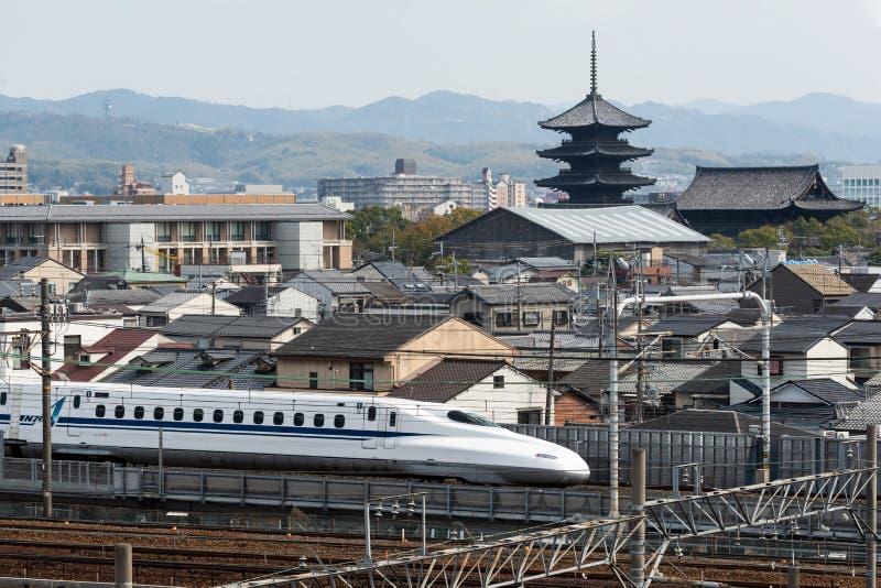 Mars 29, 2019 - Kyoto, Japan: N700 serie Shinkansen med en bakgrund av Kyoto den forntida staden, Japan royaltyfri bild