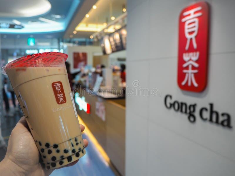 Mars 2019 - la Corée du Sud : Main femelle caucasienne tenant un thé enorme de lait de noir de taille avec des perles de Gongcha image stock