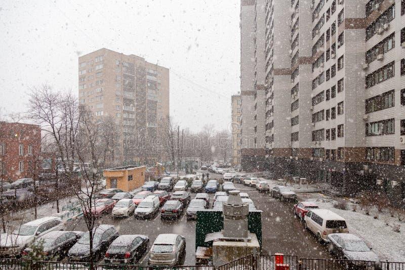 24 MARS 2019 Moskva Ryssland: plötsligt vårsnöfall över en parkeringsplats av bostads- byggnad royaltyfri bild