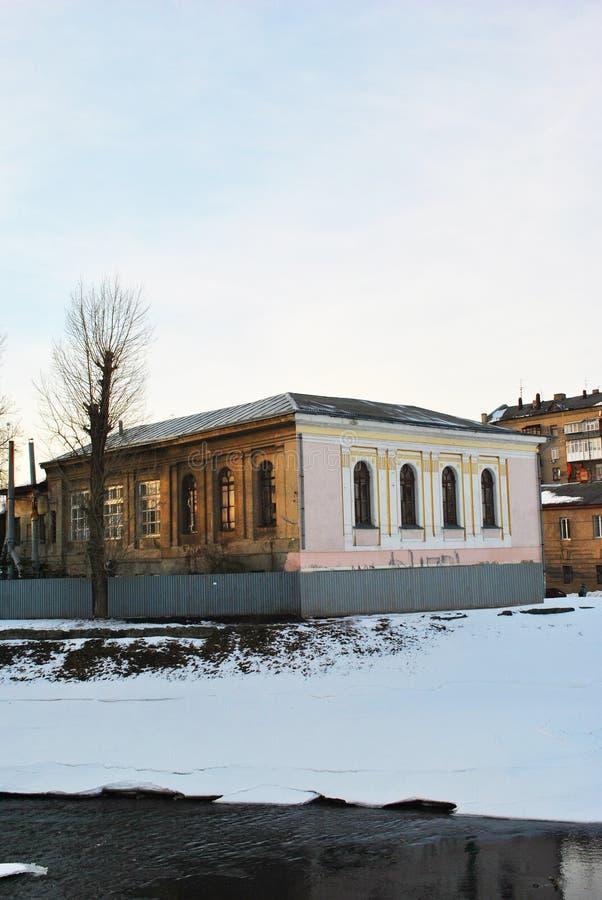 Mars 2018 : Paysage de ville, vieille maison sur le remblai de rivière, arbre sans feuilles, barrière autour, fondant la glace su photo libre de droits