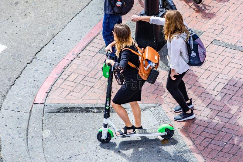Mars 19, 2019 San Diego/CA/USA - flyg- sikt av den unga kvinnan som rider en limefruktsparkcykel i i stadens centrum San Diego royaltyfria foton