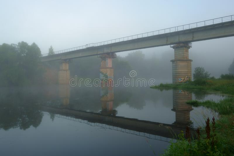 Old abandoned bridge over the river half-covered with predawn mist stock images