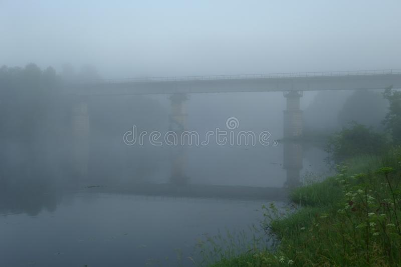 Old abandoned bridge over the river half-covered with predawn mist stock image