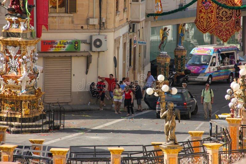 Marsa, Мальта - май 2018: Туристы и местные люди ждать на festively украшенном квадрате с флагами и статуями для ежегодного festa стоковое фото rf