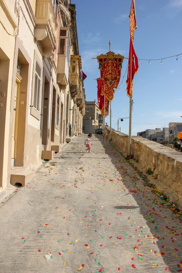 Marsa, Malta - em maio de 2018: Rua festiva decorada com as bandeiras para o feriado religioso do festa anual Menina perto de seu imagem de stock