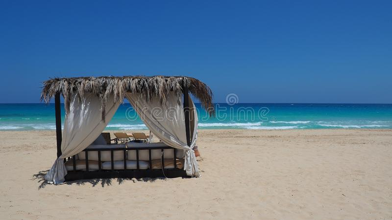 Marsa Matruh, Egypt. Elegant gazebo on the beach. Amazing sea with tropical blue, turquoise and green colors. Relaxing context. Nobody on the beach. Fabulous royalty free stock images