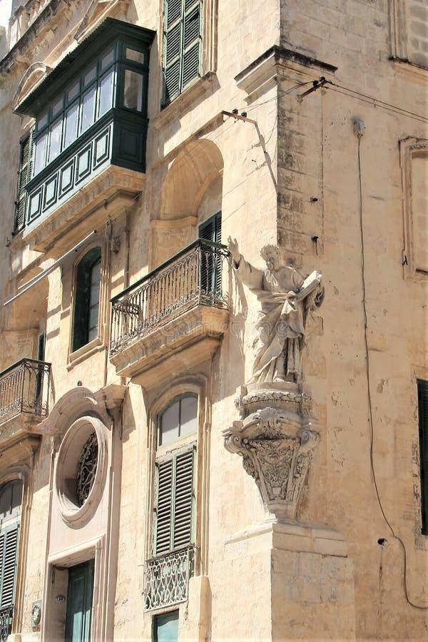Marsaskala, Malta, em julho de 2016 Estátua de Saint com um livro no canto de uma casa maltesa residencial em uma cidade pequena fotografia de stock