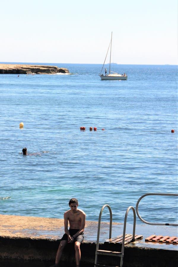 Marsaskala Malta, Juli 2016 En ensam pojke på pir mot bakgrunden av havet och yachten royaltyfri bild