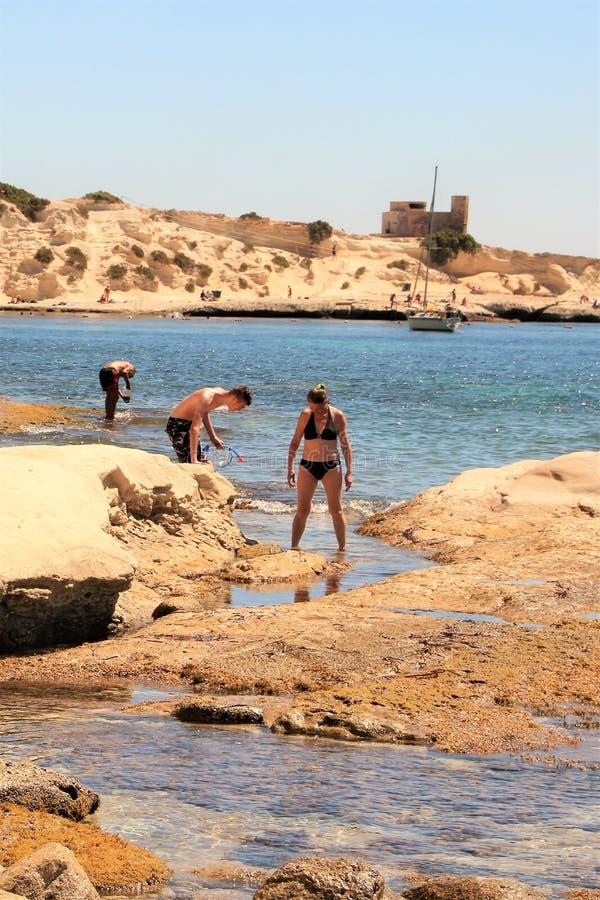 Marsaskala Malta, Juli 2016 Folk som fångar krabbor på stranden av en liten sjösidastad arkivbild
