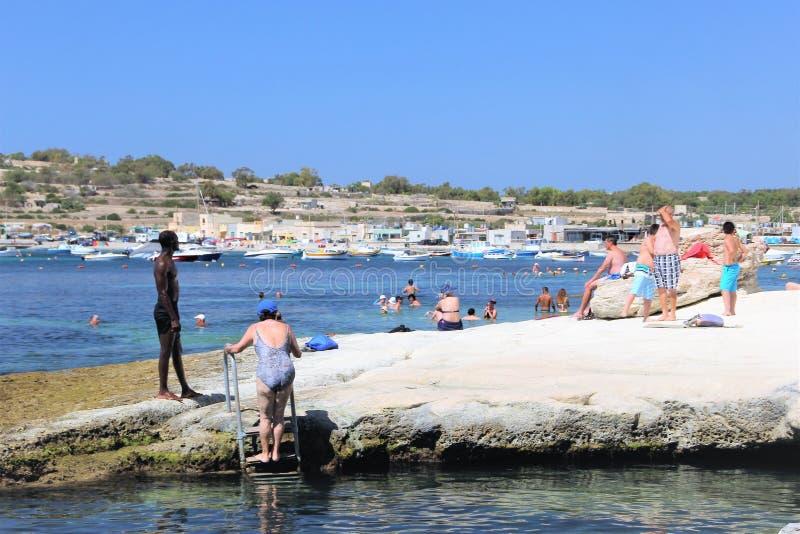 Marsaskala Malta, Juli 2016 Typisk maltesisk strand med att solbada folk i en liten semesterortstad arkivfoton