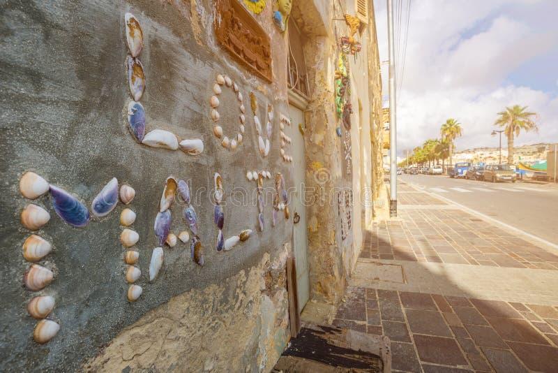 Marsaxlokk, Μάλτα - παραδοσιακά της Μάλτα ψαροχώρι και σπίτι με τα κοχύλια στον τοίχο στοκ φωτογραφία