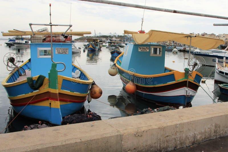 Marsaxlokk, Μάλτα, τον Ιούλιο του 2014 Οι πολύχρωμες βάρκες κατά μήκος του αναχώματος κλείνουν επάνω στοκ φωτογραφία