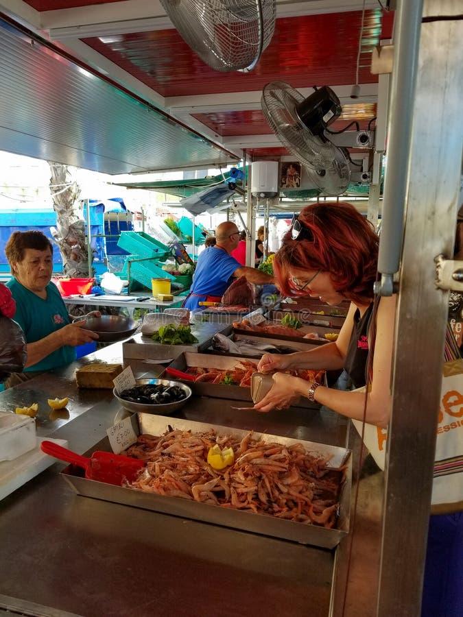 Marsaxlokk, Мальта - май 2018: Женщина с волосами имбиря идет оплатить на fishmarket для креветок стоковое изображение