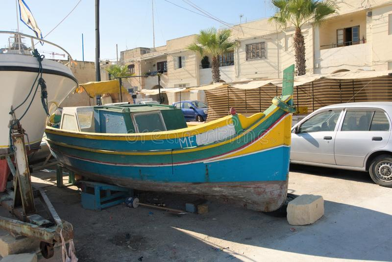 Marsaxlokk, Malta, August 2019. A vintage fishing boat pulled ashore as part of a cityscape. royalty free stock photo