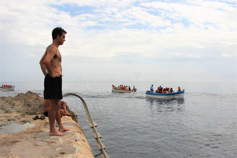 Marsaxlokk, Malta, em julho de 2014 Povos em uma praia maltesa típica na perspectiva do mar e em barcos com turistas fotos de stock royalty free