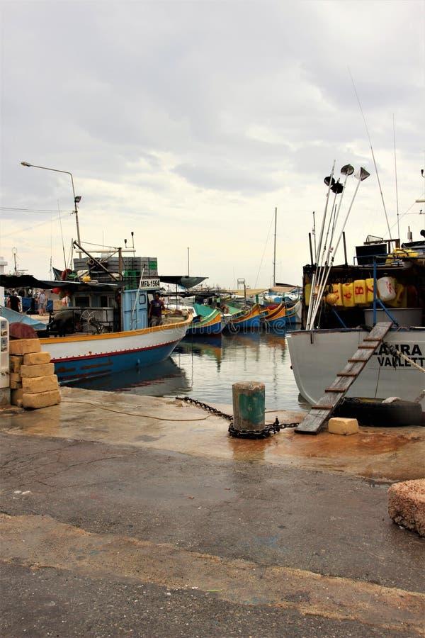 Marsaxlokk, Malta, luglio 2014 Barche per la pesca nella sera al pilastro dopo la pioggia fotografie stock