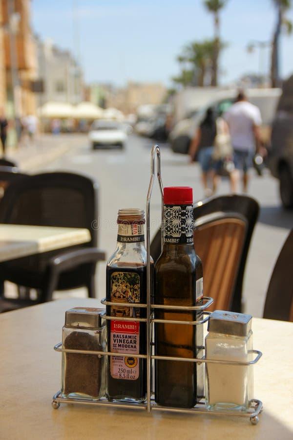 Marsaxlokk, Malta - Mai 2018: Gewürzbalsamico-essig, Salz, Pfeffer und Olivenöl auf dem Tisch im Sommerstraßencafé stockbild