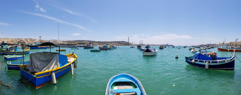 Marsaxlokk, Malta - Mai 2018: Panoramablick des Fischerdorfes mit traditionellem gemustertem Boote luzzu lizenzfreie stockfotos