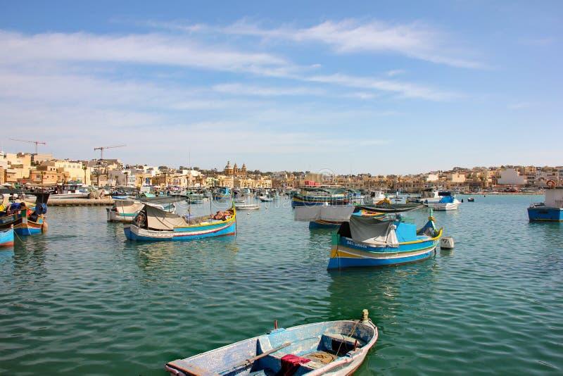 Marsaxlokk, Malta - Mai 2018: Panoramablick des Fischerdorfes mit traditionellem gemustertem Boote luzzu stockfotografie