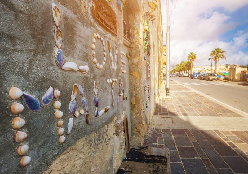 Marsaxlokk, Malta - paesino di pescatori e casa maltesi tradizionali con le coperture sulla parete fotografia stock libera da diritti