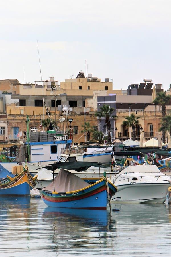 Marsaxlokk, Malte, ao?t 2015 Bateaux de pêche couverts pour la nuit sur le bord de mer dans la vieille ville photographie stock