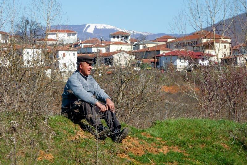 Marschera 25th 2011, Korestia, Grekland - gamal mansammanträde på jordningen och att stirra, nära den Korestia byn, Kastoria, Gre arkivfoto