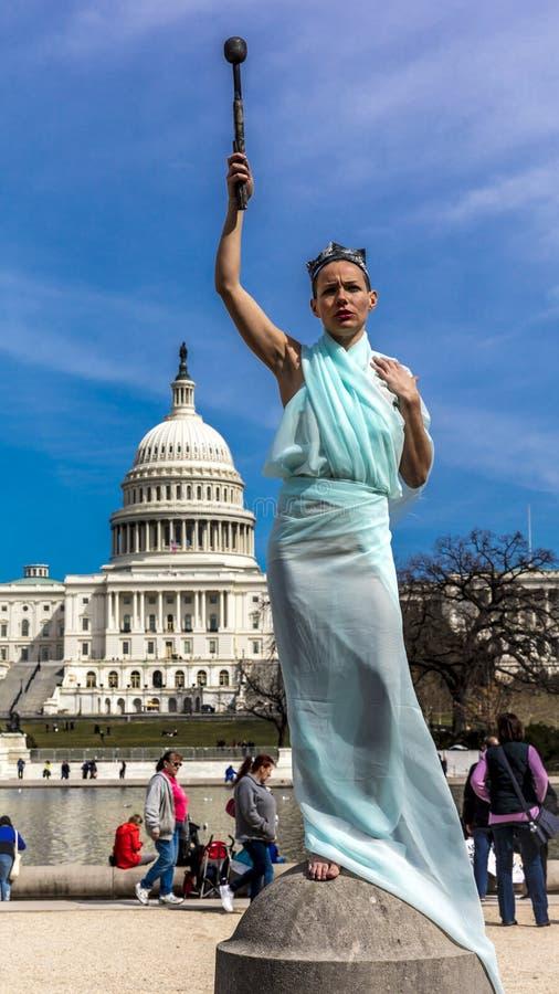 MARSCHERA 24, 2018 - Washington DC, kvinnlig poserar som statyn av frihet framme av USA-Kapitolium, Staty bakgrund arkivbilder