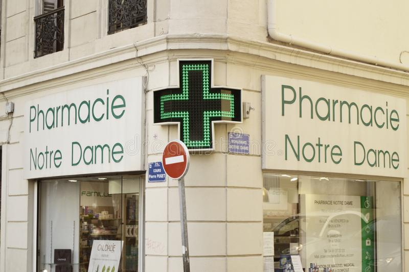 Marseille, France - October 12, 2018: close-up of led green cross, pharmacy symbol, at the corner of Mediterranean architecture royalty free stock images