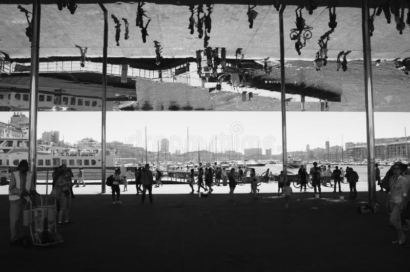 MARSEILLE FRANKRIKE - JUNI 24, 2016: Folket går under takstrukturen för den reflekterande spegeln som göras av polerat stål, plan arkivbild