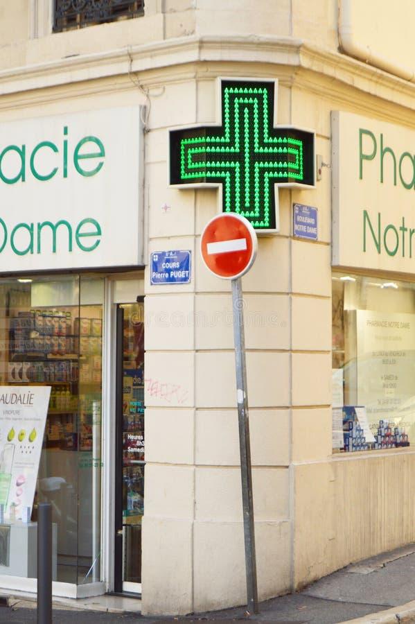 Marseille Frankrike - Oktober 12, 2018: närbild av det ledde gröna korset, apoteksymbol, på hörnet av medelhavs- arkitektur royaltyfri fotografi