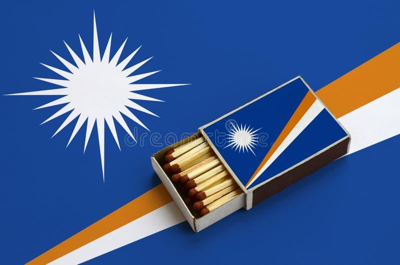 Marshall Islands-de vlag wordt getoond in een open lucifersdoosje, dat met gelijken wordt gevuld en op een grote vlag ligt stock illustratie