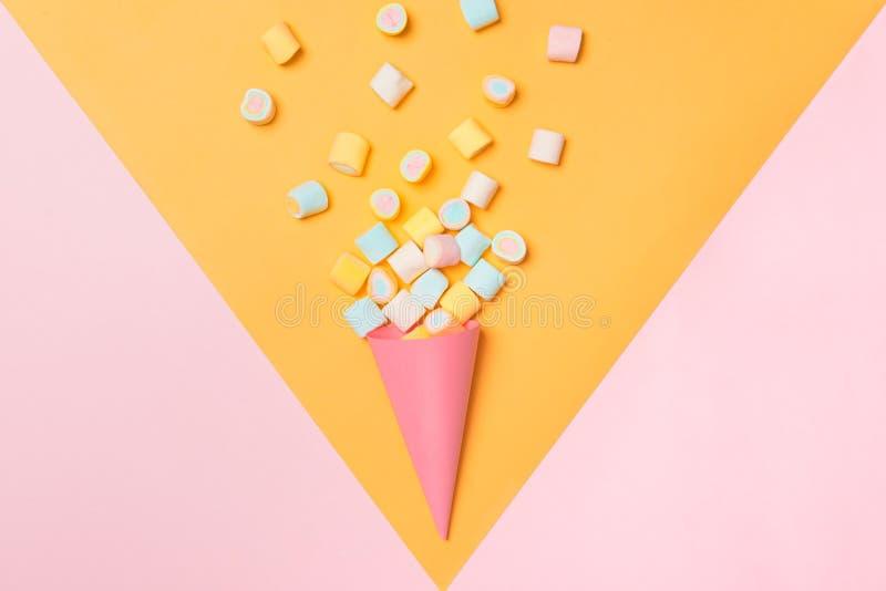 Marshmallow ζωηρόχρωμη κατάταξη καραμελών σε έναν κώνο παγωτού στο ρόδινο και κίτρινο υπόβαθρο που αντιμετωπίζεται άνωθεν Gummy π στοκ εικόνες