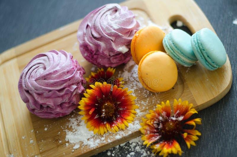 Marshmallow και macaroons με τα λουλούδια και ψεκάζουν στοκ φωτογραφίες