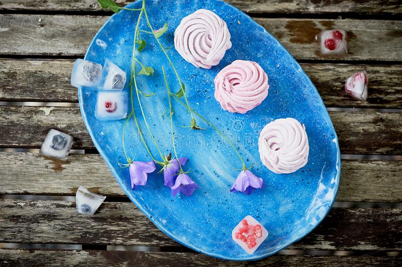 The marshmallow on a blue sky plate. Light dessert.Delicate wildflowers. And frozen in the ice berries stock photography