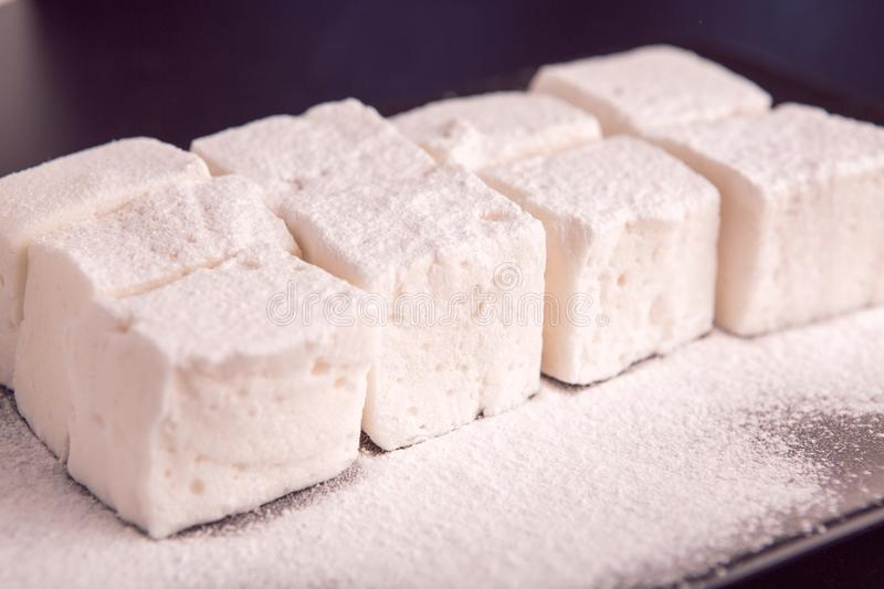 Marshmallow cubes on black plate stock images